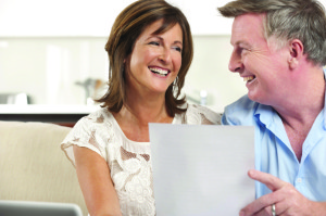 Mature couple smiling reading a document at home